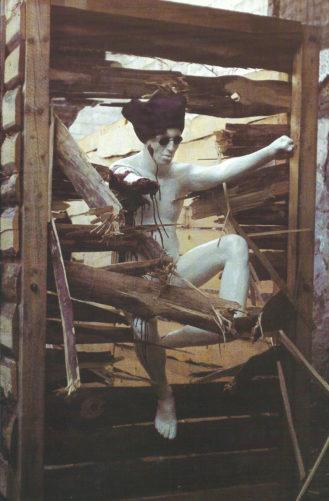 Figur, einarmig, mit drei Knien und einzehigem Fuß durchbricht eine Bretterwand