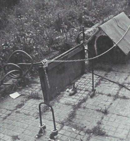 Eisenobjekt mit Hundehütte, Kindersocken und Kette